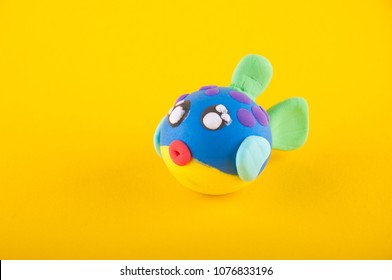 Nice puffer fish made of colorful modelling clay laying on yellow background