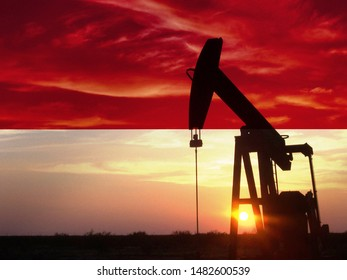 Nice pumpjack oil extraction and cloudy sky in sunset with Indonesia flag.