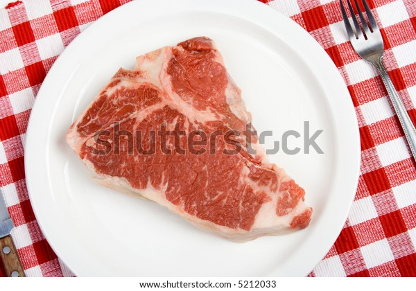 A nice, raw T-bone steak on a plate. Perfect for that rare steak lover!