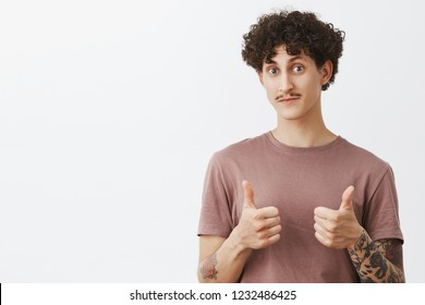 Nice really like it. Surprised and impressed good-looking stylish male friend with moustache and curly hairstyle showing thumbs up raising eyebrows and nodding in approval gesture being supportive