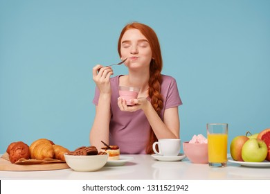 Nice red-haired girl trying tasting cherry yogurt wirh a teaspoon, closed her eyes from pleasure, sitting at the table during lunch, pastries on the table and fresh fruit, against a blue background.