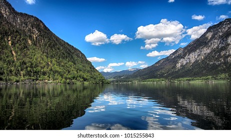 Nice reflection of forest, blue sky, and mountain on lake at Hallstatt, Austria. View from boat.