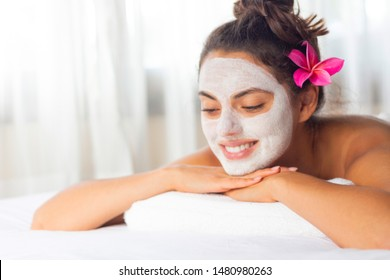 Nice relaxing young woman with white mask on face lying down on towel on bench spa with flower on hair. Smiling on camera.