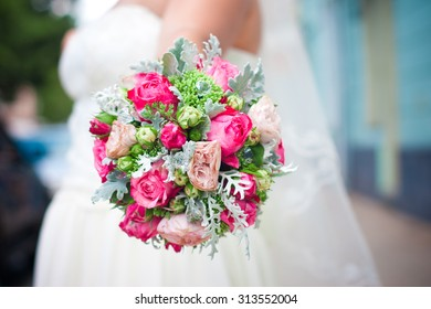 Nice round colorful bouquet of bride with crimson and pink flowers and cleft cabbage