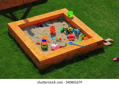 A nice sandbox playground filled with lots of toys. Surrounded by green grass, seen from top.