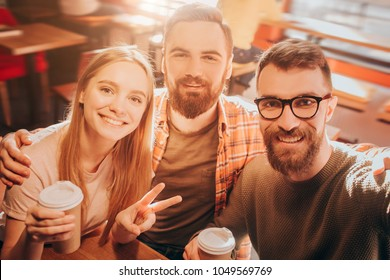 Nice selfie of two men and one woman sitting together very close and posing on camera. The girl shows the symbol of peace with her fingers. Cut view.