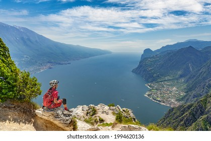 nice senior woman with elctric mountain bike resting at Punta Larici and enjoying the awesome view over Garda Lake between Riva del Garda and Torbole