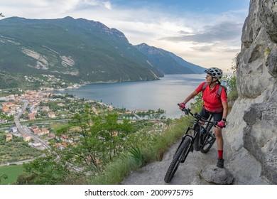 nice senior woman with electric mountain bike resting on Monte Brione and enjoying the awesome view over Garda Lake between Riva del Garda and Torbole