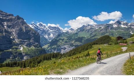 nice senior woman riding her e-mountainbike on the Lauberhorn downhill, down from Kleine Scheidegg to Wengen and Lauterbrunnen, Jungfrauregion,Switzerland