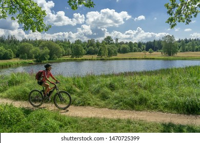 nice senior woman riding her electric mountain bike along the Weiherwiesen Lake on the Swabian Alb near Heubach, Baden Wuerttemberg, Germany