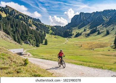 nice senior woman riding her electric mountain bike up to the Schreiber Sattel below Winterstaude summit in the Bregenzer Wald mountain range in Vorarlberg, Austria - Shutterstock ID 1821980378