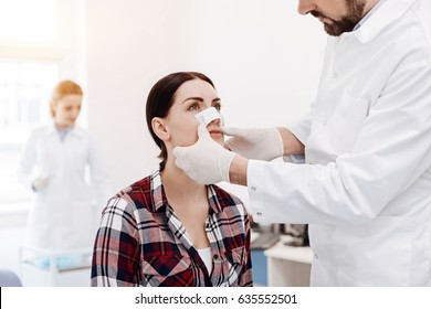 Nice serious woman having a medical dressing on her nose
