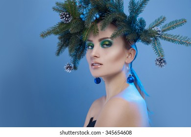 Nice serious woman with xmas tree-wreath on head looking at camera on blue background in studio
