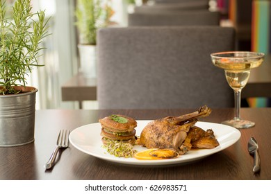 Nice served dishes (prawns and duck) with coctails on the restaurant table