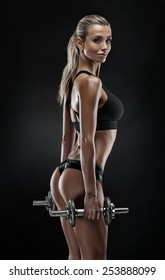 Nice sexy woman doing workout with dumbbell isolated over black background