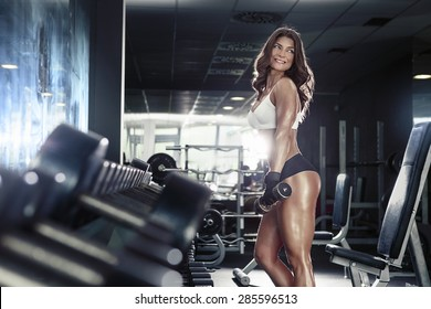 Nice sexy woman doing workout with dumbbells  in gym