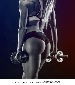 Nice sexy woman doing workout with dumbbells over black background