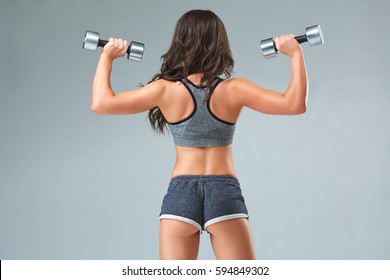 Nice sexy woman doing workout with dumbbells isolated over gray background