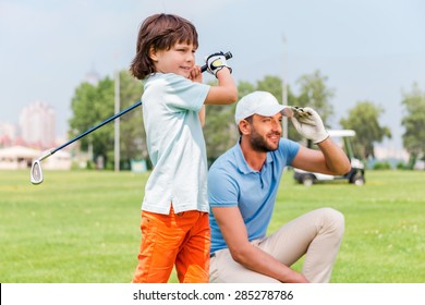 Nice shot! Confident little boy playing golf while his father standing close to him on the golf course