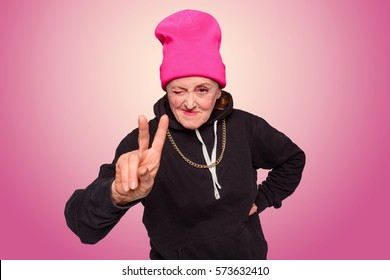 Nice shot of gangsta granny. An old woman went off the rails and dressed in hip-hop style, her mood is uplifted: she winks and shows a peace sign. Radial pink to white gradient in the background.