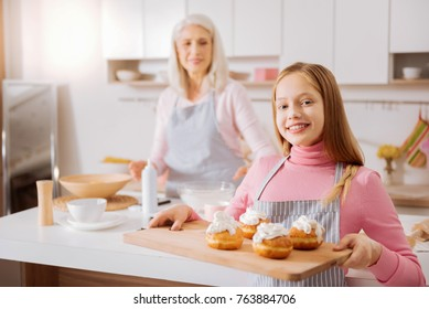 Nice skillful pretty girl standing in the kitchen and smiling while presenting her bakery