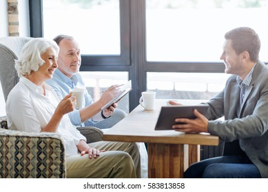 NIce smiling aged couple having meeting in the cafe