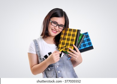 Nice smiling Asian school girl wearing nerd glasses, posing with some books and pen, on white background