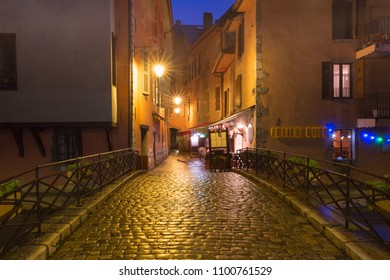 Nice street and bridge over Thiou river in Old Town of Annecy at rainy night, France