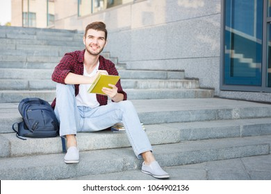 Nice student sitting on the stairs and writing notes to his notebook, preparing for exams, smiling at the camera having a rest in the university campus outdoors. Education concept, copy space