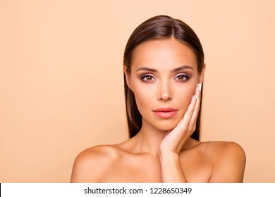 Nice stunning adorable good-looking lady with her naked shoulders she isolated on pastel beige background with copy space for text she touch her cheek by hand