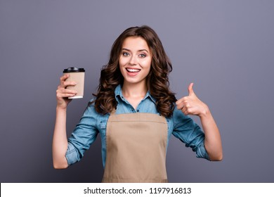 Nice stylish adorable positive cheerful sweet winsome lovely attractive girl, barista with wavy hair in casual denim shirt and apron, rest, pause, relax, showing thumb-up, isolated on grey background