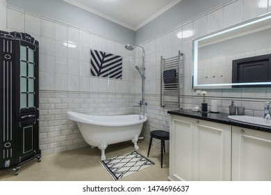 Nice stylish bathroom with cupboard, mirror and tub