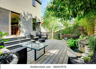 Nice summer backyard with exotic landscape. View of wicker chairs with ottoman and glass top table