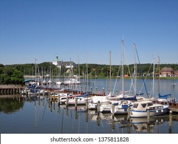 Nice summer view of Schlei fjord with small sailing boats in the foreground. Schleswig, northeastern part of Schleswig-Holstein, Germany. Gottorf Castle in the background