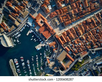 Nice sunny cityscape of old Dubrovnik with houses with shingled roofs, churches, fortification walls and a pier with many yachts and boats. People are walking on streets. Top view horizontal photo.