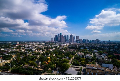 A nice sunny day with a few puffy clouds aerial drone view of Houston , Texas mega city downtown skyline cityscape in the distance amazing day in October