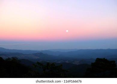 Nice sunset scene over misty mountains range with visible silhouettes through the evening colorful.