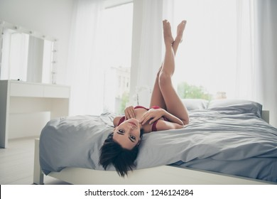 Nice sweet lovely attractive feminine perfect girl long legs wearing red maroon lingerie lying on bed linen sheets upside-down in white light room