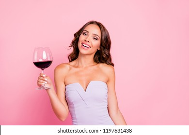 Nice sweet tender gentle adorable attractive gorgeous flirty cheerful wavy-haired girl in white cocktail dress, holding wine-glass, isolated over pink background
