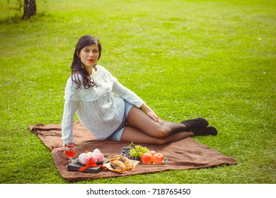 Nice sweet woman dressed in a white sweater, shorts on a picnic sits on the green grass and enjoys a good mood and day