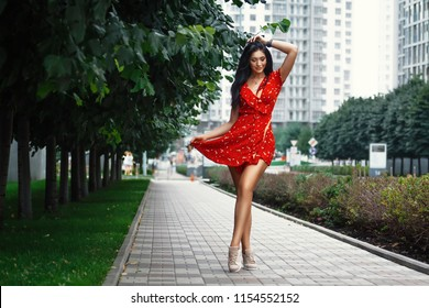 Nice tanned stylish brunette girl in red short dress with flowers is standing poses and flirting walking on the street city
