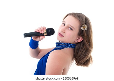 Nice teen girl with microphone, singing. smiling little girl in blue dress. portrait of a happy little girl playing, isolated on white background.