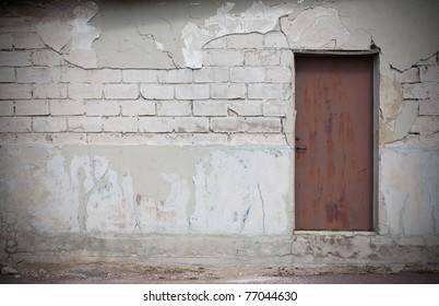 Nice textured wall, big white bricks , plaster fallen off, rusty metal door.