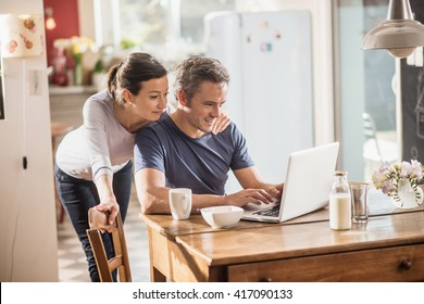 Nice thirty year couple using a laptop while having breakfast in the kitchen, they are wearing casual clothes and th man has gray hair