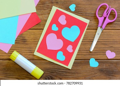 Nice Valentines day card with paper hearts, scissors, glue stick, colored paper sheets on a wooden background. Creative Valentines day card crafts. Easy paper craft projects. Top view