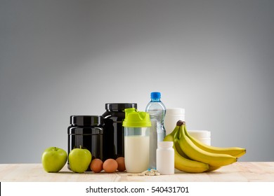 Nice variant of nutrition for staying fit and healthy. Great set of amino acid complex, protein and creatine for sportsmen. Fresh fruits and three eggs with a bottle of mineral water on the table.