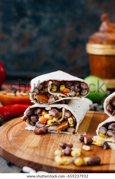 Nice vegetarian burrito over black table on wooden board