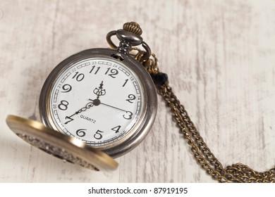 Nice vintage pocket watch on wooden background