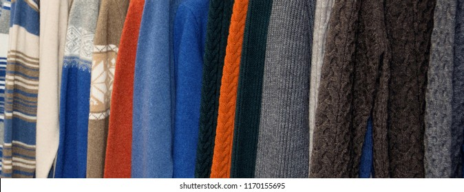 Nice warm colorful sweaters hang on hangers inside of a shopping mall. Beautiful clothes for winter autumn season. Fashion industry for men. Wool things for fall. Classic design. Merchandise in a shop