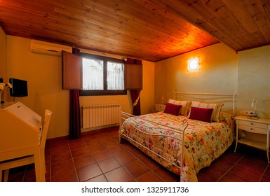 Nice warm interior of bedroom in a rustic style in country house or hotel. Wooden beams and walls made of natural stone. Mediterranean style home.